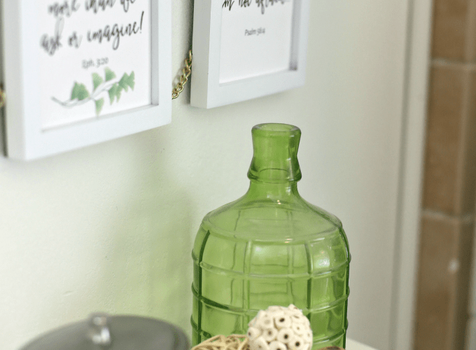 scripture in frames on wall green bottle with natural elements and jar on white counter
