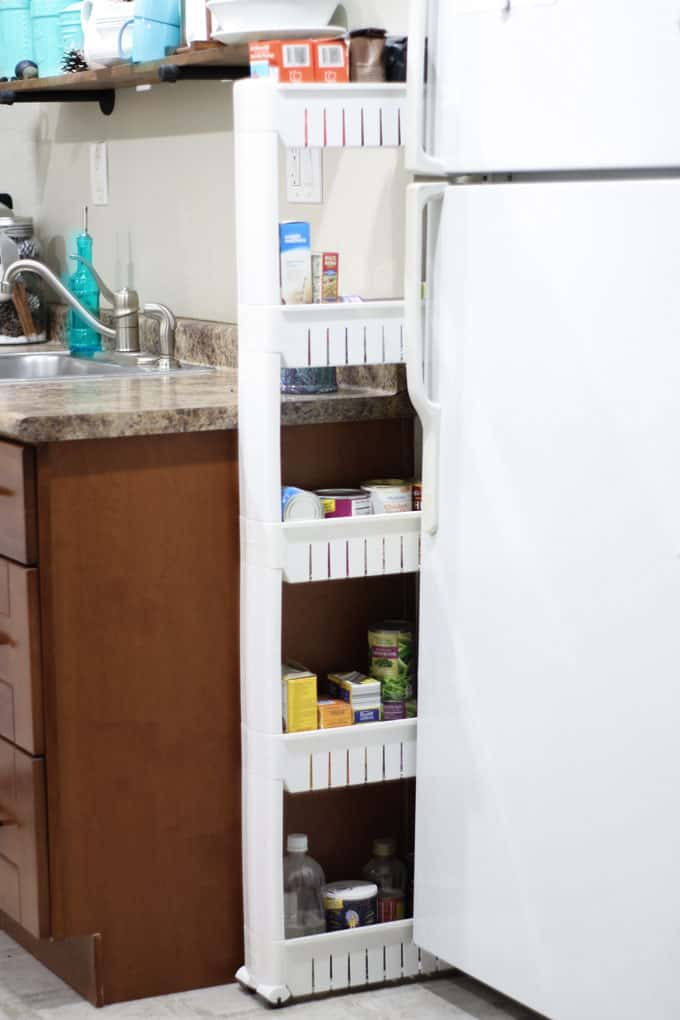 white plastic tiered tower with canned goods between wall and refrigerator