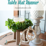 easy stenciled cork table mat runner with candlestick and wood beads and wooden stool with green wreath