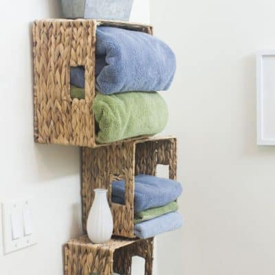 affordable storage solutions small bathrooms three wicker baskets with towels and decor items mounted to wall
