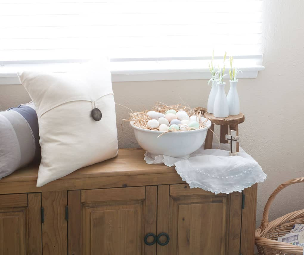 spring home tour decor ideas curating a home window bench with pillows and large bowl of pastel eggs with mini stool and white bottles