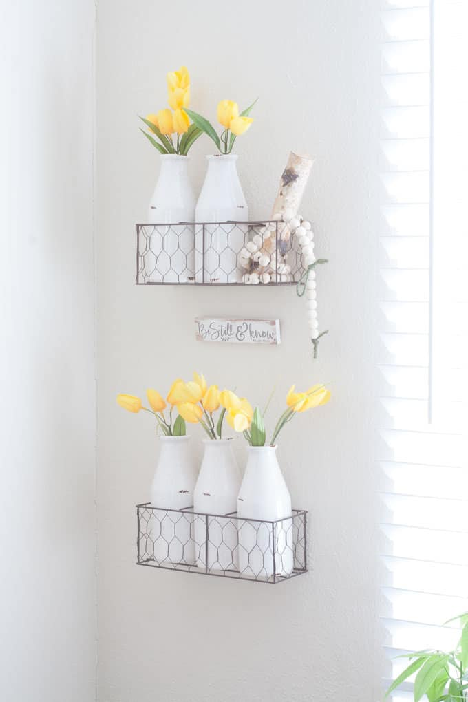 spring home tour decor ideas curating a home tow baskets on wall with milk bottles vases and tulips birch branches and beads