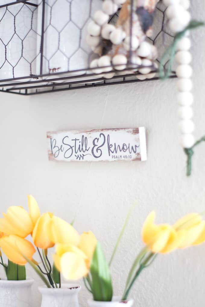 spring home tour decor ideas curating a home yellow tulips and hanging beads in wire baskets with sign that says be still and know
