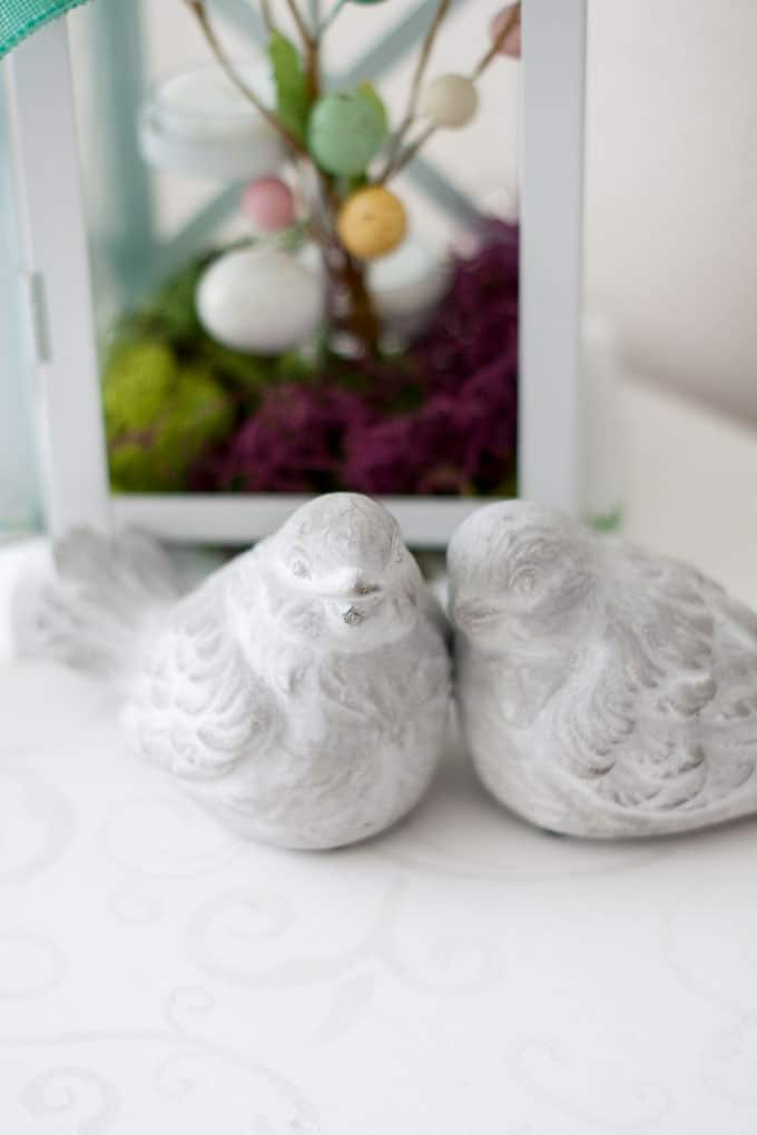 spring home tour decor ideas curating a cement birds and white lantern with moss and eggs on white surface with gray detail