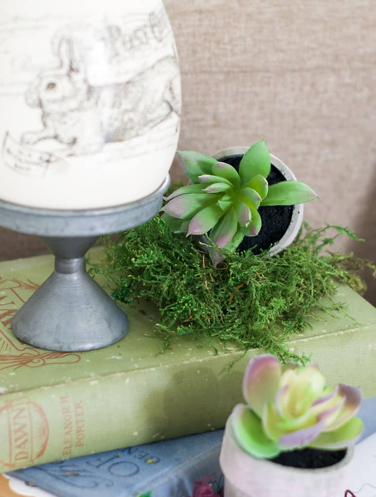 spring home tour decor ideas curating a home vintage book with easter bunny egg and succulents with moss on white surface