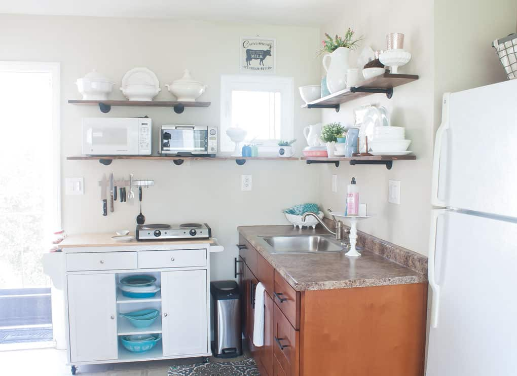 spring home tour and the comparison trap small kitchen with open shelving and white dishes with decor on it portable island with dishes and white refrigerator