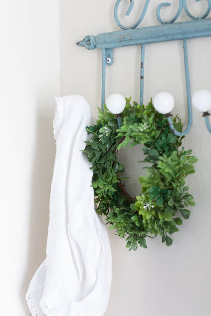 spring home tour part 1 comparison trap boxwood wreath hanging on iron wall hooks with linen on side