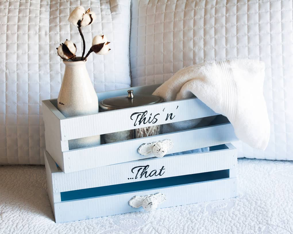 diy farmhouse utility crate shelves two blue crates with white handles on a bed with a milk bottle cotton stem and towel with words this n that in black