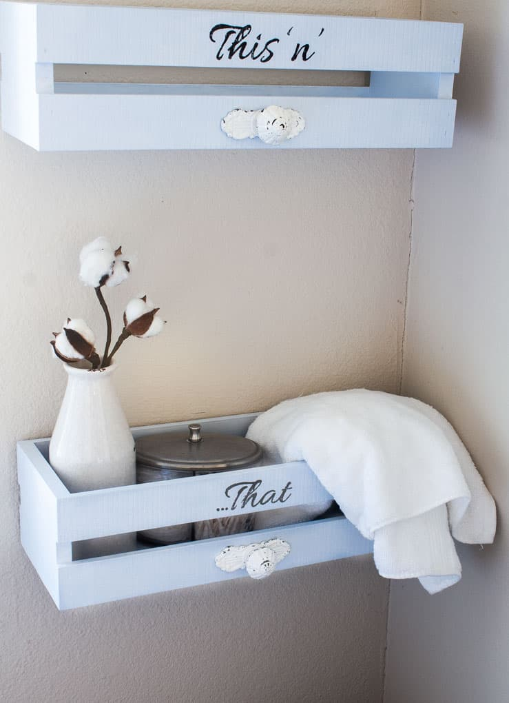 diy farmhouse utility crate shelves two blue crates with white handles with a milk bottle cotton stem and towel with words this n that in black on wall