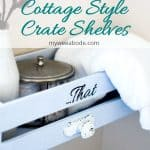 diy farmhouse crate shevles blue crate shelf with white knob lettering says that with white towel milk bottle and silver lid title cottage style crate shelves