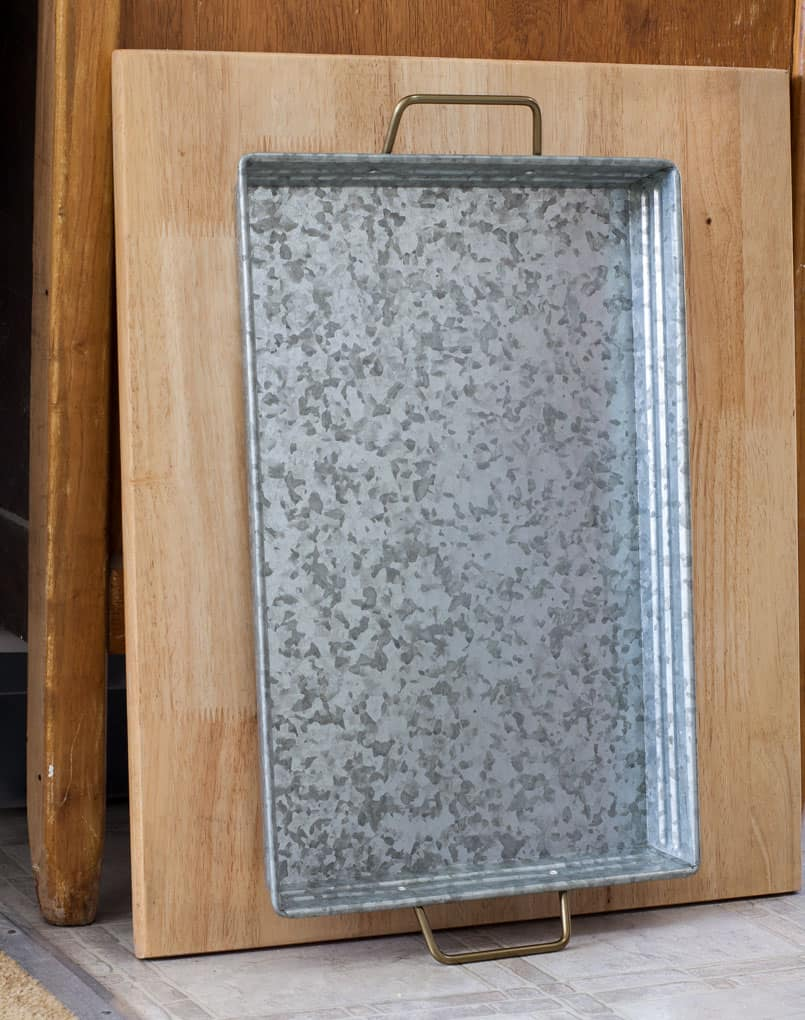 galvanized metal tray with handles displayed in front of a cutting board
