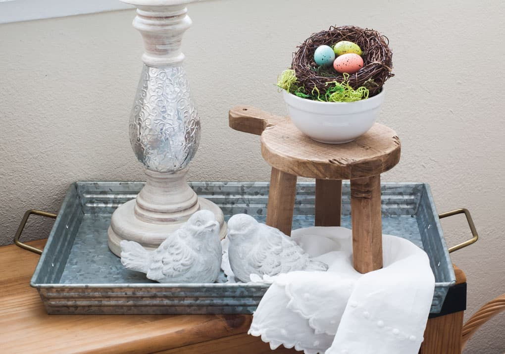 A galvanized tray with handles holding a candle holder miniature stool nest bowl and cement birds on a wood bench