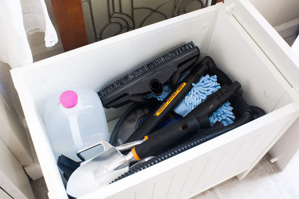 Inside the IKEA Silveran white storage bench filled with Homeright Steam Cleaner and accessories