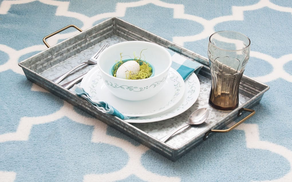 a metal tray holding a table setting napkin and decorative egg
