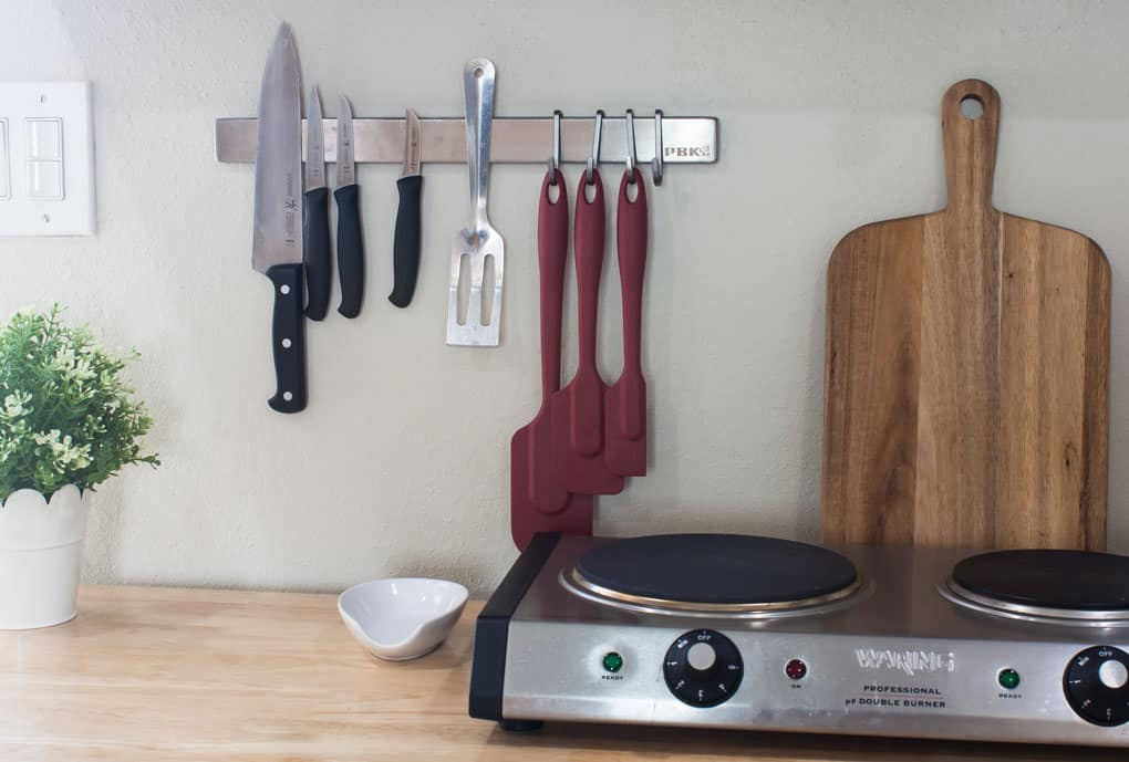 A kitchen island counter holding a double burner spoon rest cutting board and magnetic strip on the wall with utensils
