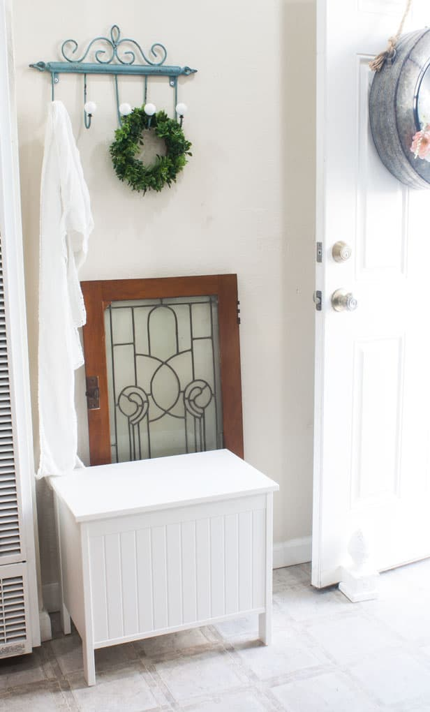 An entry way door opens to a mudroom nook with a seating bench lead glass window hooks and decorative items