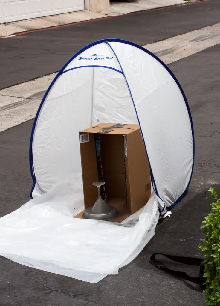 spray shelter sitting on asphalt with box and cake plate inside