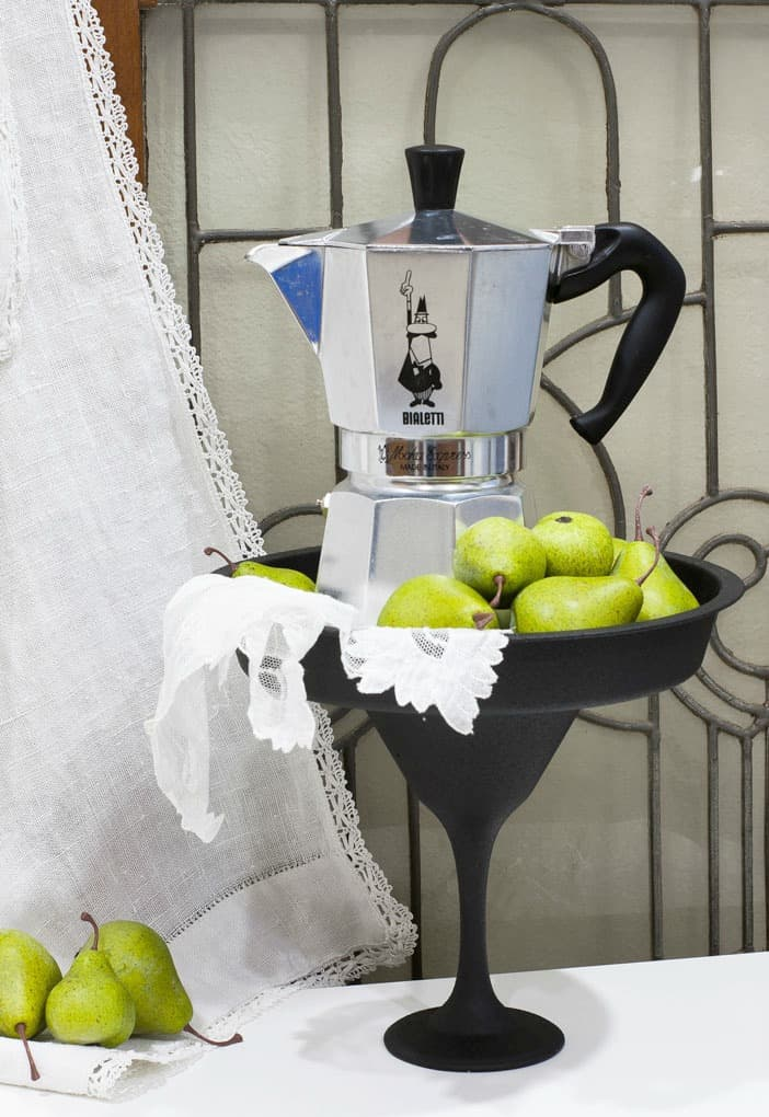 black cake plate with espresso coffee pot pears and linen cloth with leaded glass window in background