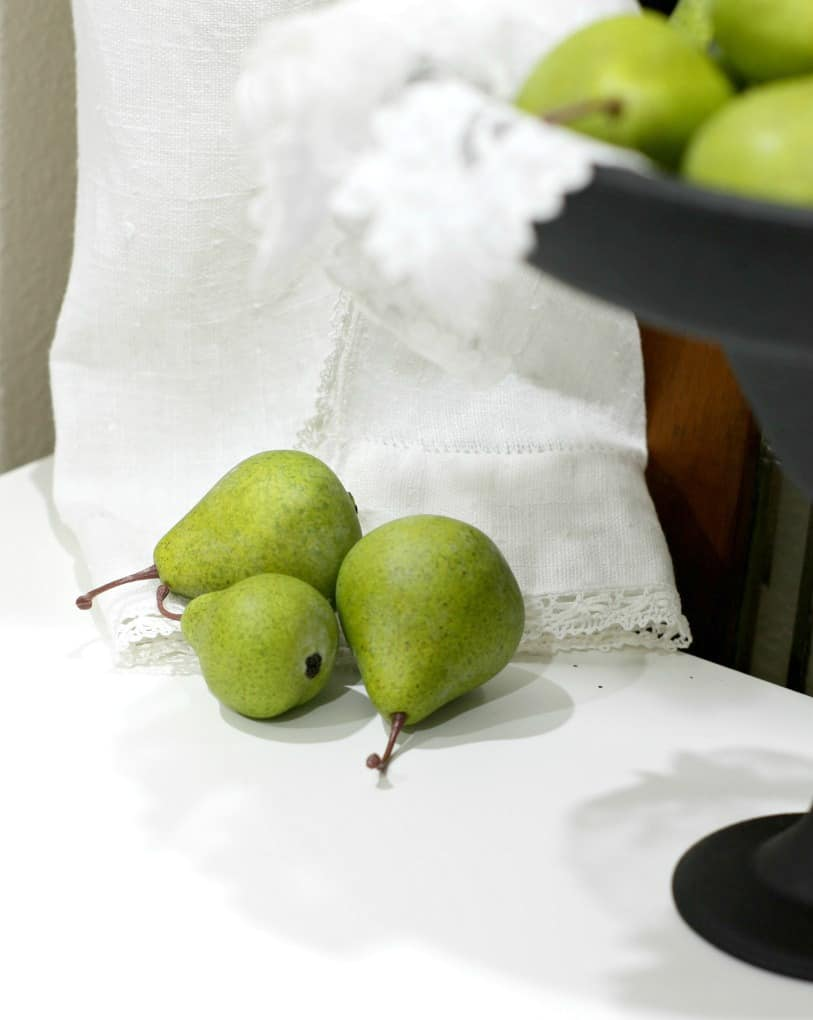 pears reasting on linen apron with cake plate on the side
