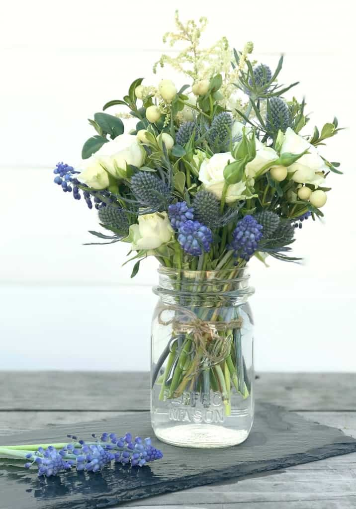 blue yellow floral arrangement in mason jar on table