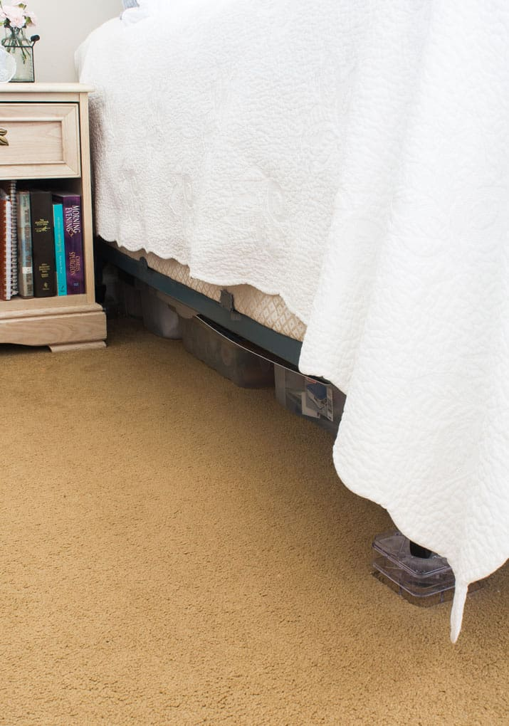 gold carpet night stand view under bed with white cover
