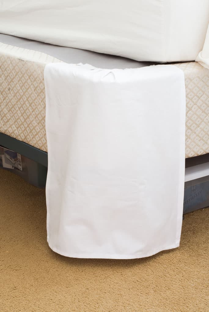 white fabric panel pinned to corner of box spring
