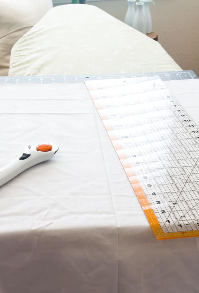rotary cutter and straight edge laying on white fabric with ironing board