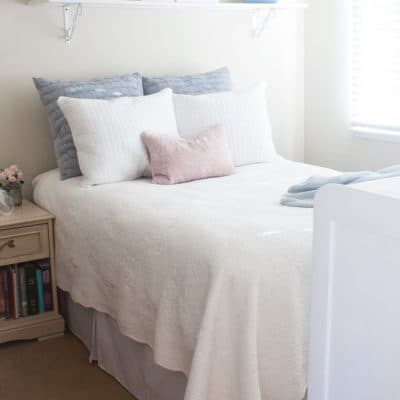 bedroom with bed and nightstand with white blue pink bedding