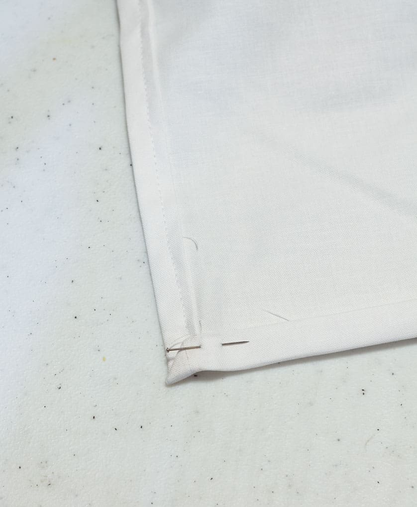 corner of white material with straight pin inserted