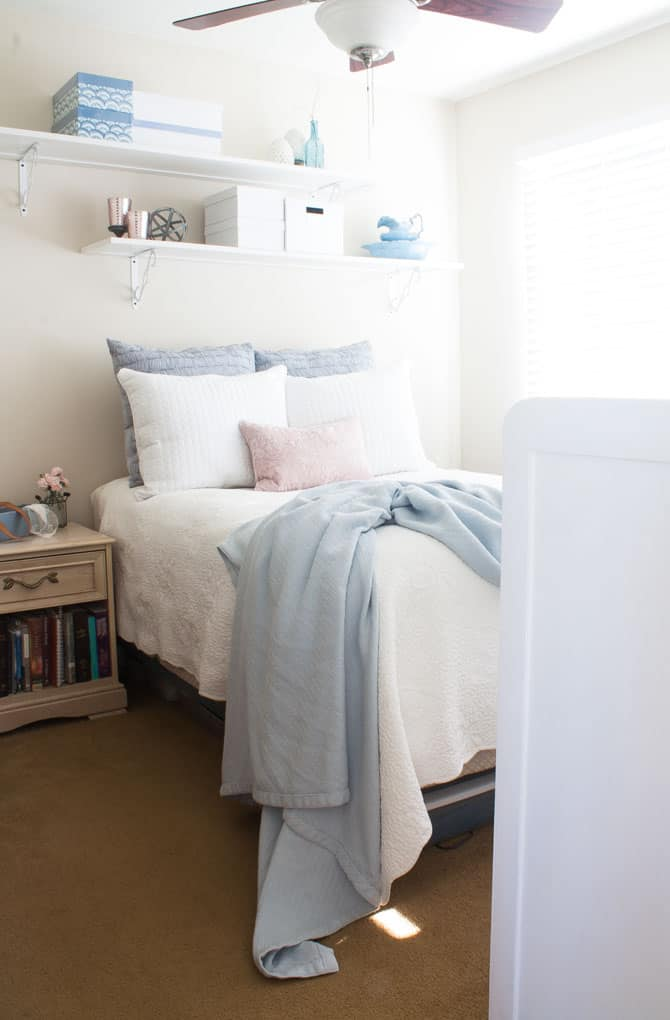 bedroom with white and blue bedding pink pillow nightstand with books and wall shelves
