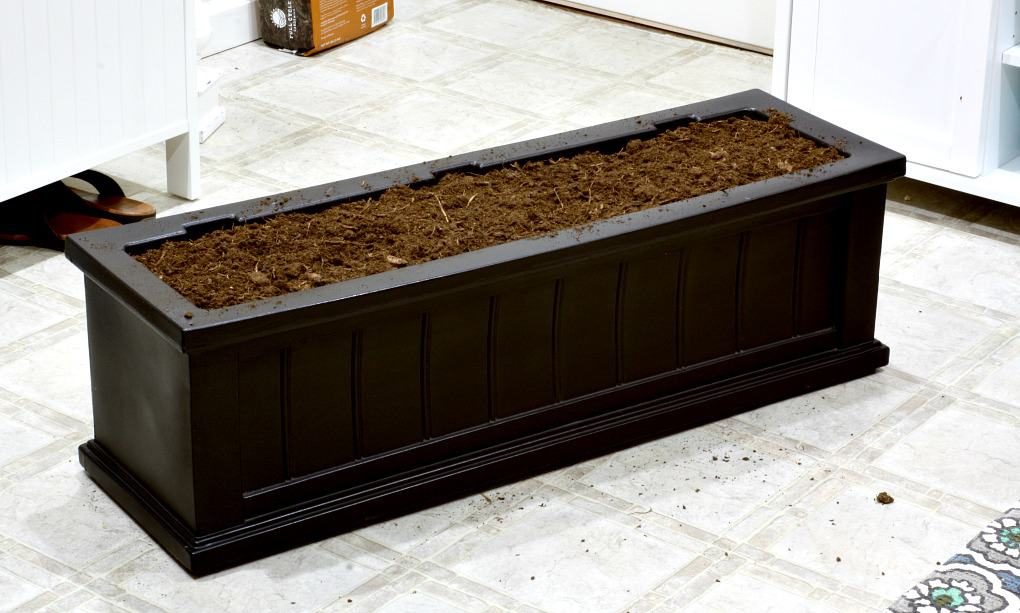 black window box filled with soil on kitchen floor