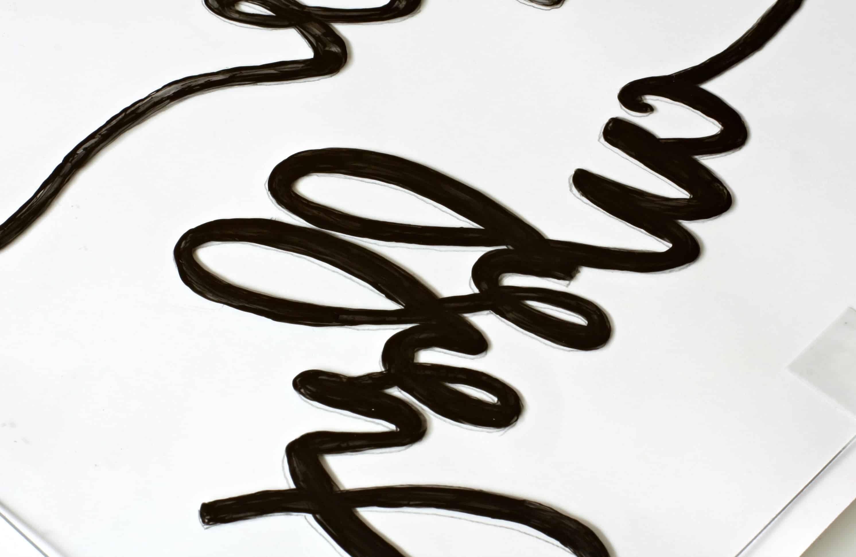 paper and glass sitting on table with lettering painted on the paper