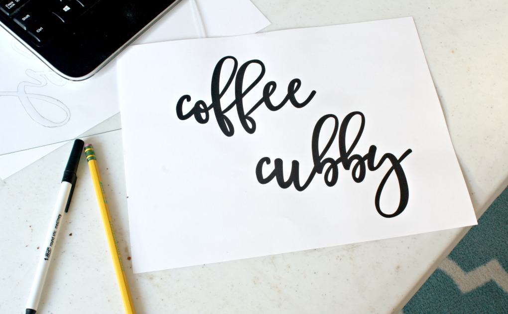 paper sitting on table printed in lettering font that says coffee cubby with pencil on the side