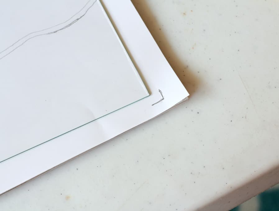 paper and glass sitting on table with pencil marks