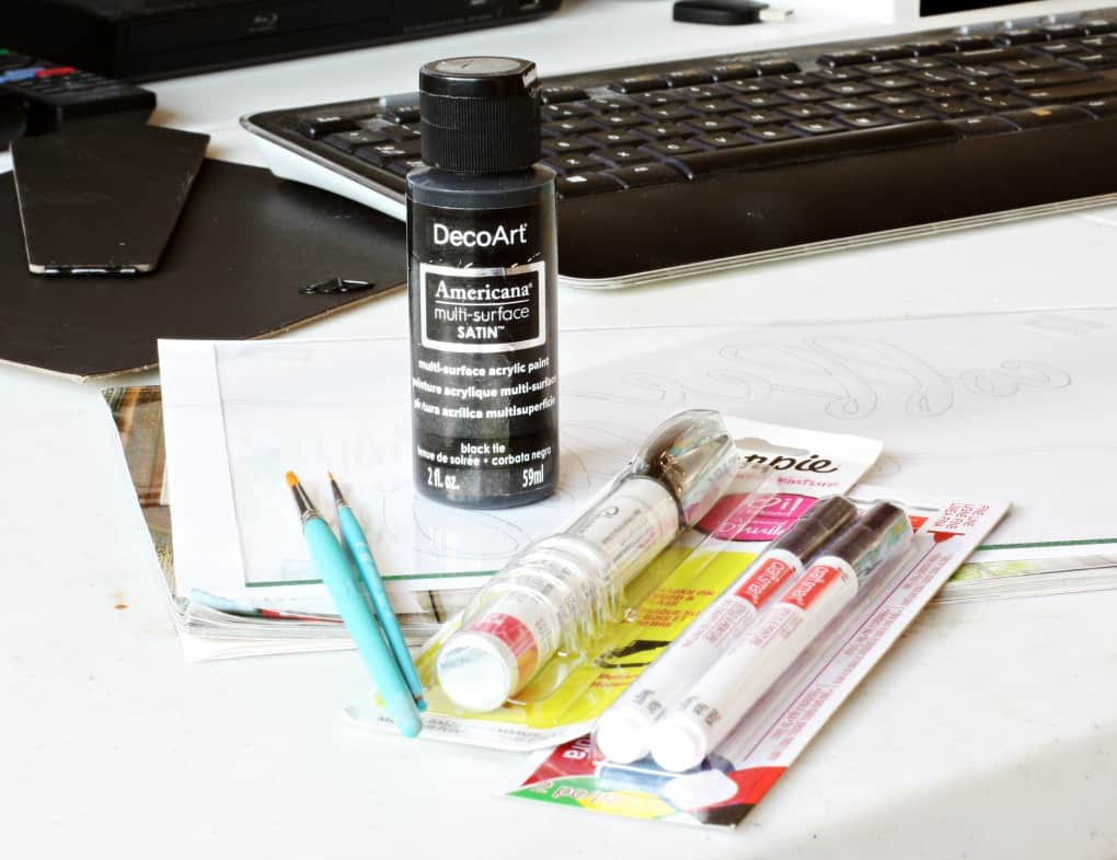Paint brushes and paint pens sitting on table with papers and keyboard