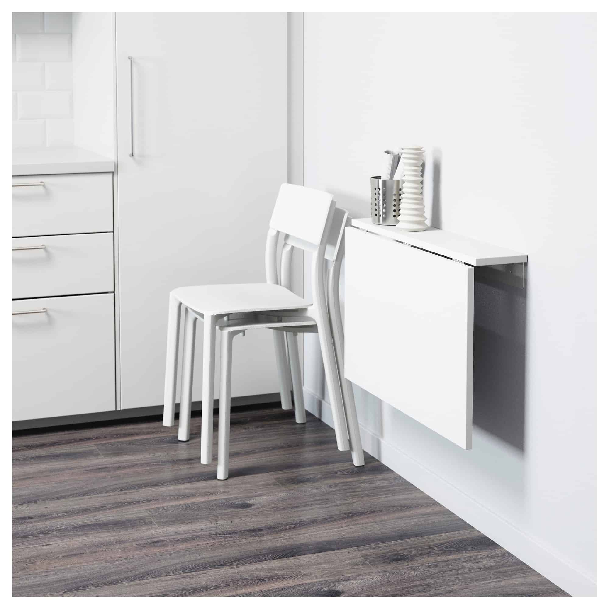 white drop leaf table with two chairs and decor in a white room