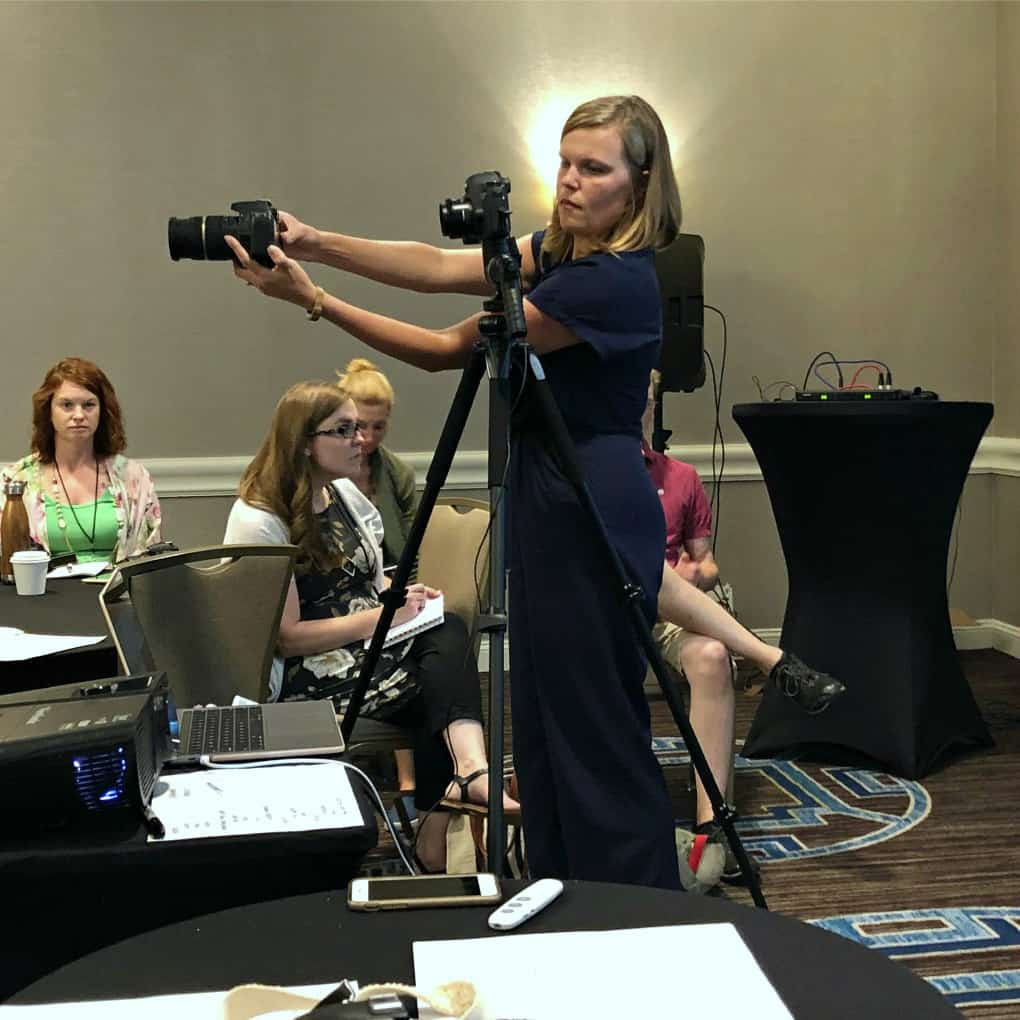woman standing in front of class teaching photography with camera on tripod