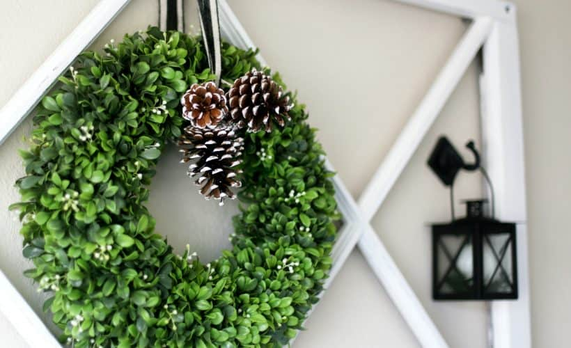 boxwood wreath with pinecones and black lantern hanging on white window frame