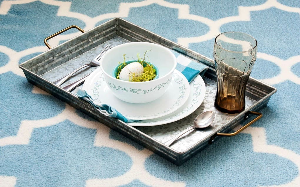 galvanized tray with dinner place setting and napkin with egg inside bowl on aqua and white rug