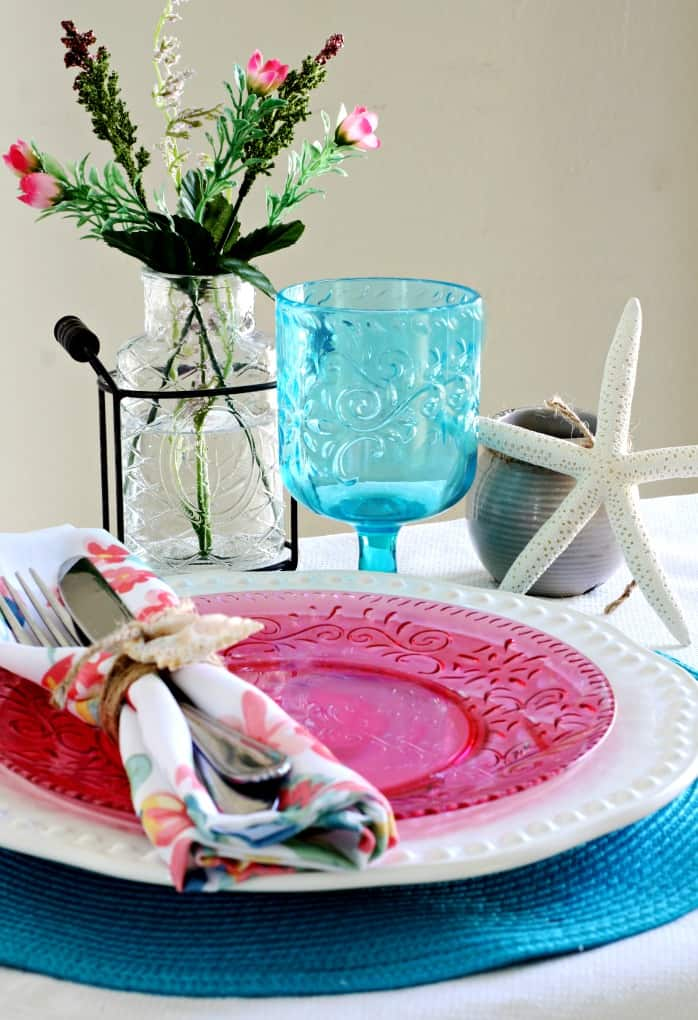 tablesetting on table with white tablecloth teal placemat pink and white dish napkin goblet with flower vase and starfish
