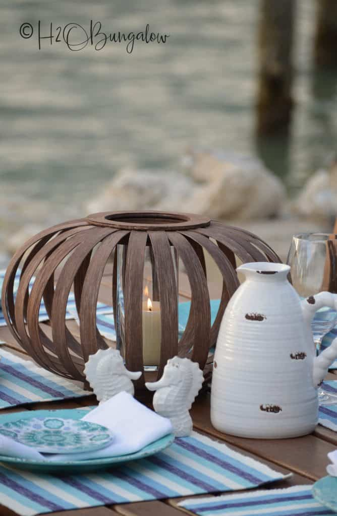 wooden lantern with candle white seahorses and white pot on table