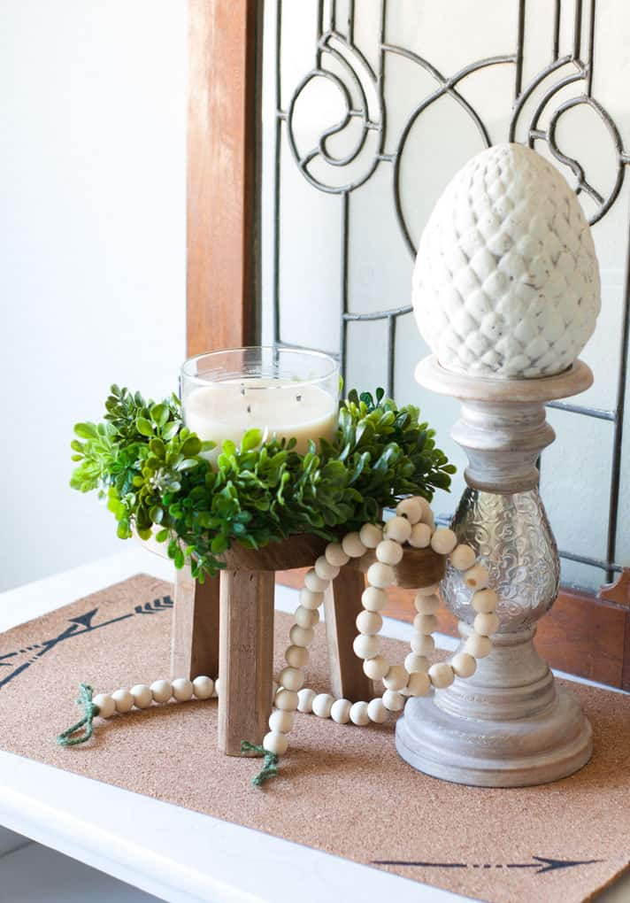 stool wreath candle candle holder beads ceramic acorn leaded glass window sitting on cork mat
