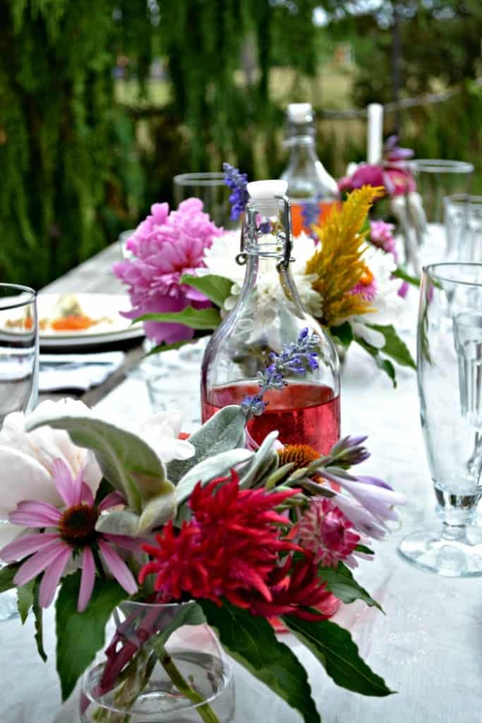 table with white linen runner, glass containers flowers decanter with beverage and table setting