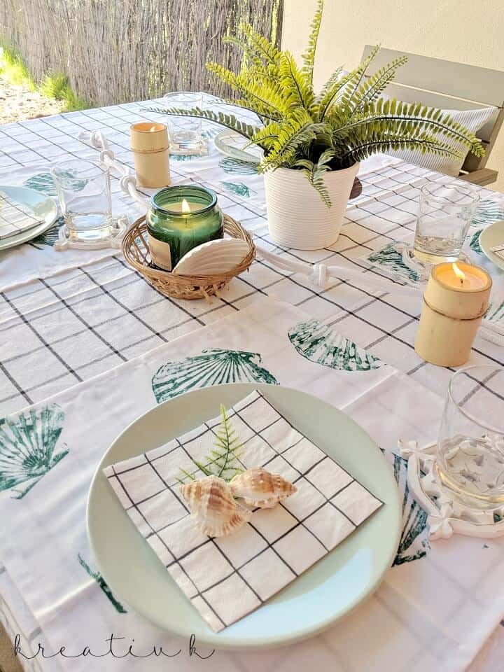 table with checked tablecoth and green and white table setting with candles and plants