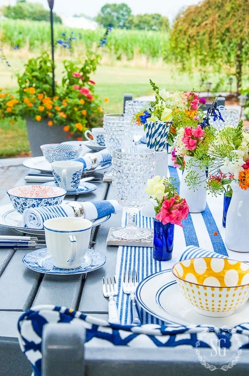 table with blue and white accessories dishes flowers bowls and plates