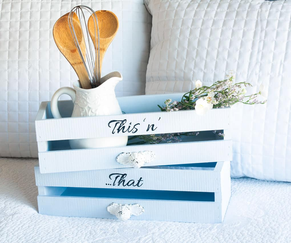 blue crates sitting on white cloth and white pillows white pitcher with utensils lavender sitting in crate