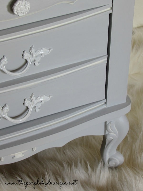gray dresser with ornate feet and handles