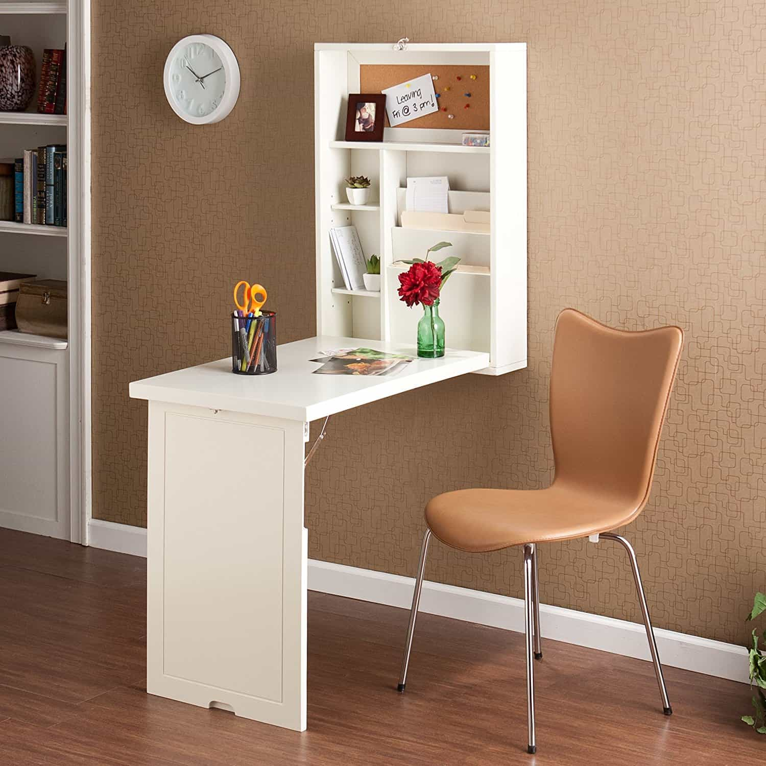 white wall mounted fold out desk with tan chair decorative items on desk tan wall with white clock
