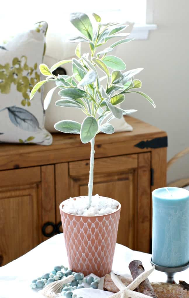 topiary tree in terra cotta pot with aqua candle sitting in metal candle holder birch branches and wooden bead garland on white table