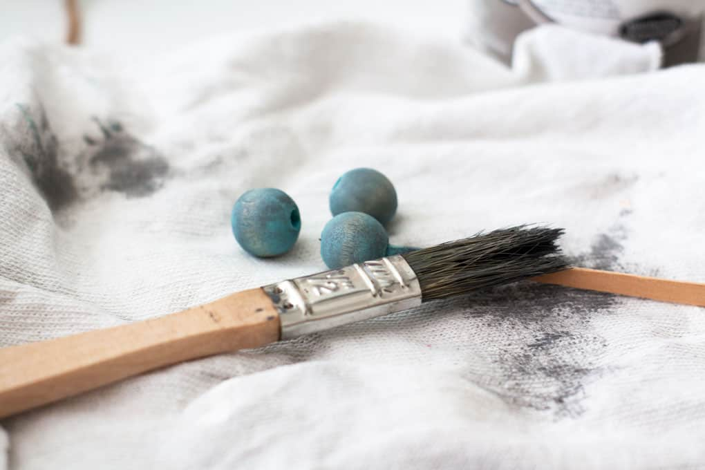 paint brush with aqua beads on white cloth